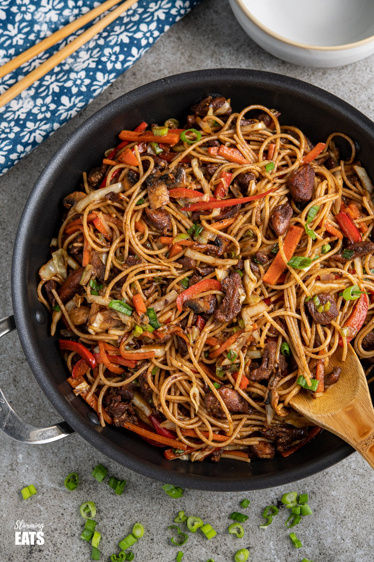 chicken with noodles and vegetables in a black frying pan with scattered spring onions