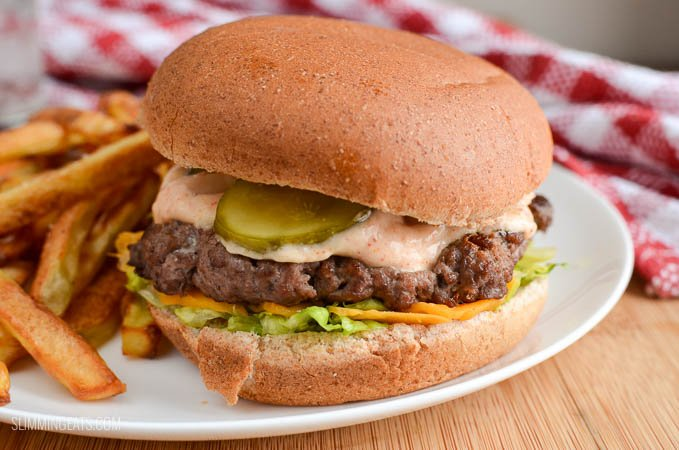 close up of lighter version of big mac and fries fakeaway on a white plate with glass of water and red and white napkin