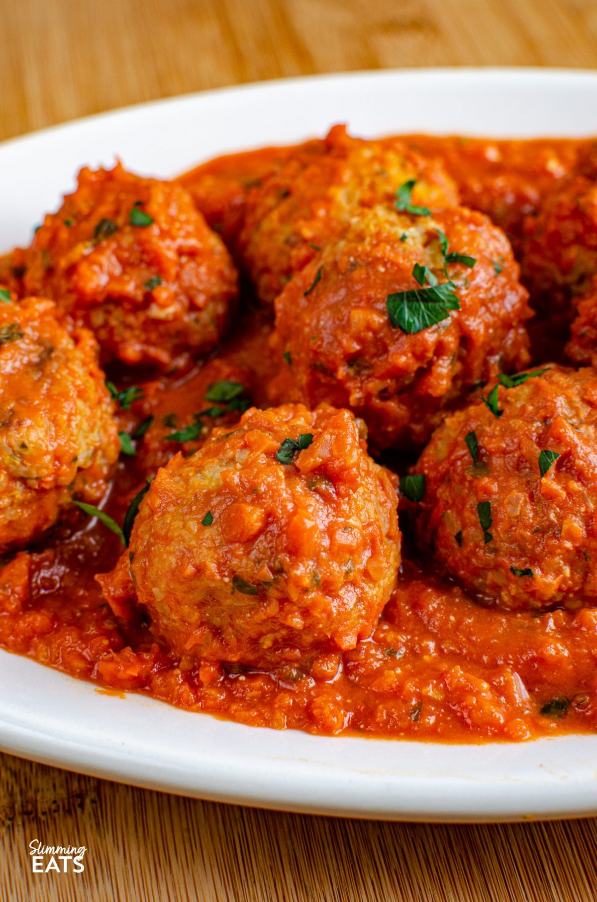 close up of Vegetarian Meatballs in Creamy Tomato Sauce  on white oval plate