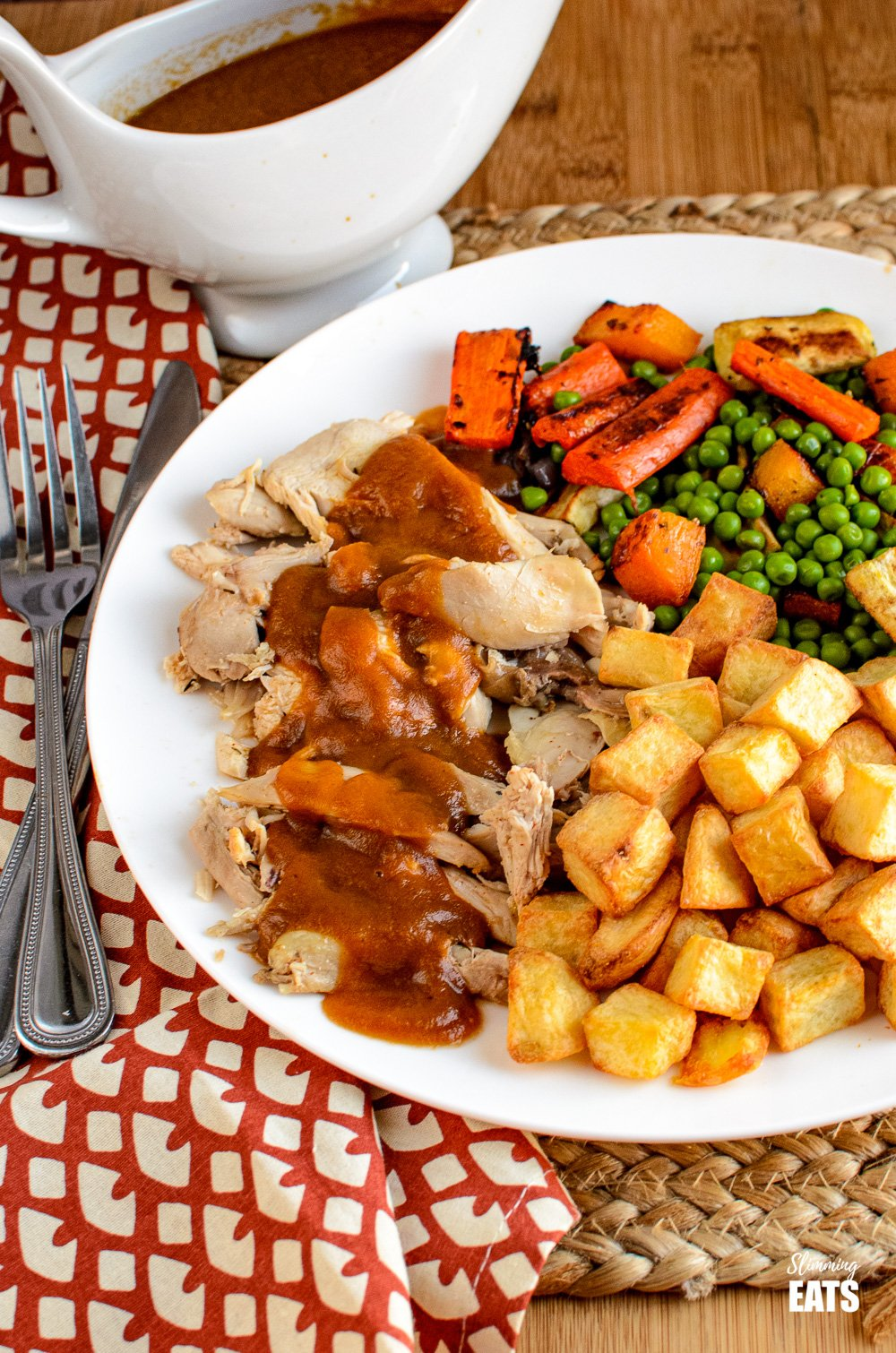 instant pot cooked whole chicken on plate with vegetables, drizzled with gravy