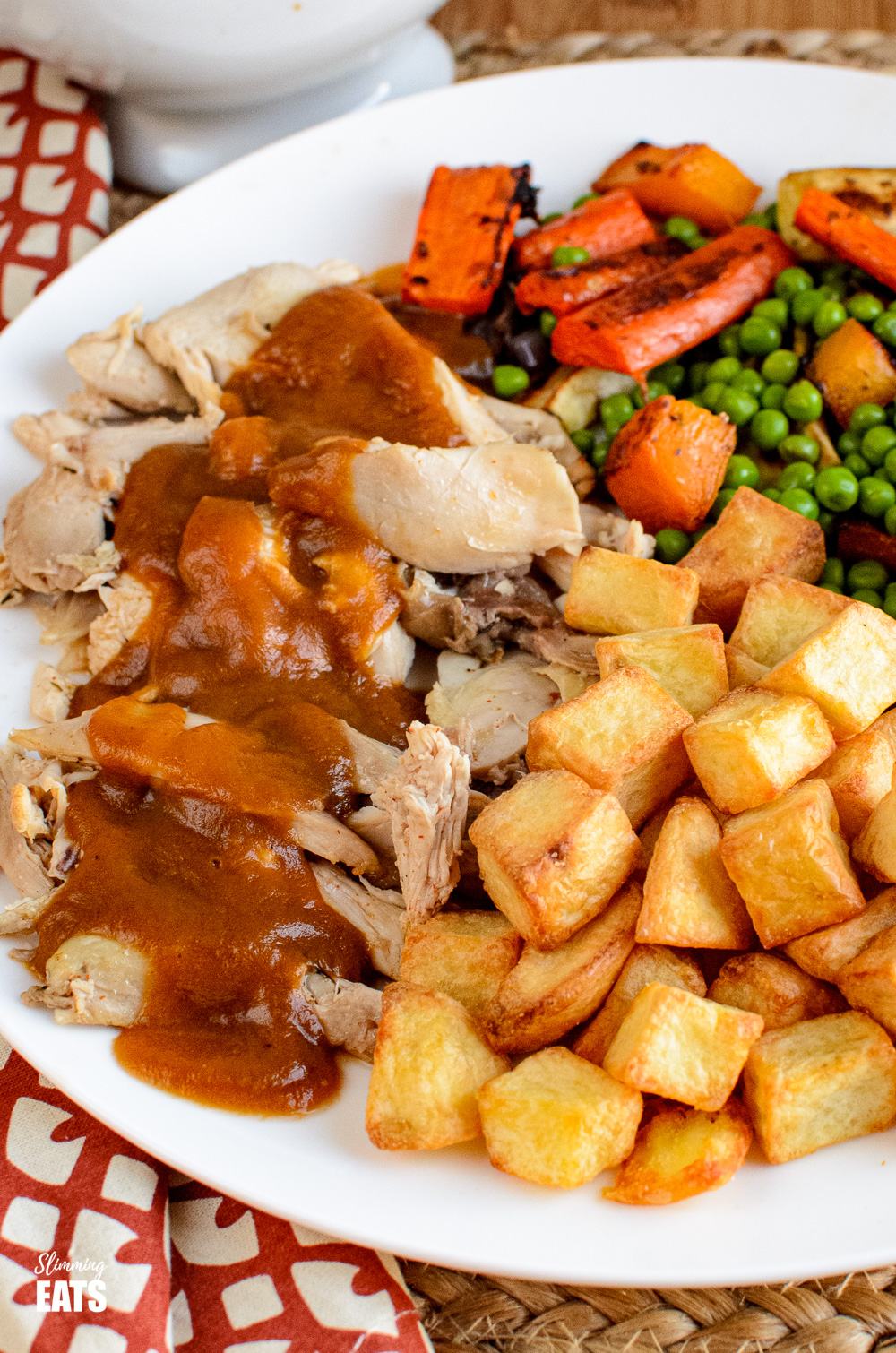 close up of instant pot cooked whole chicken on plate with vegetables, drizzled with gravy