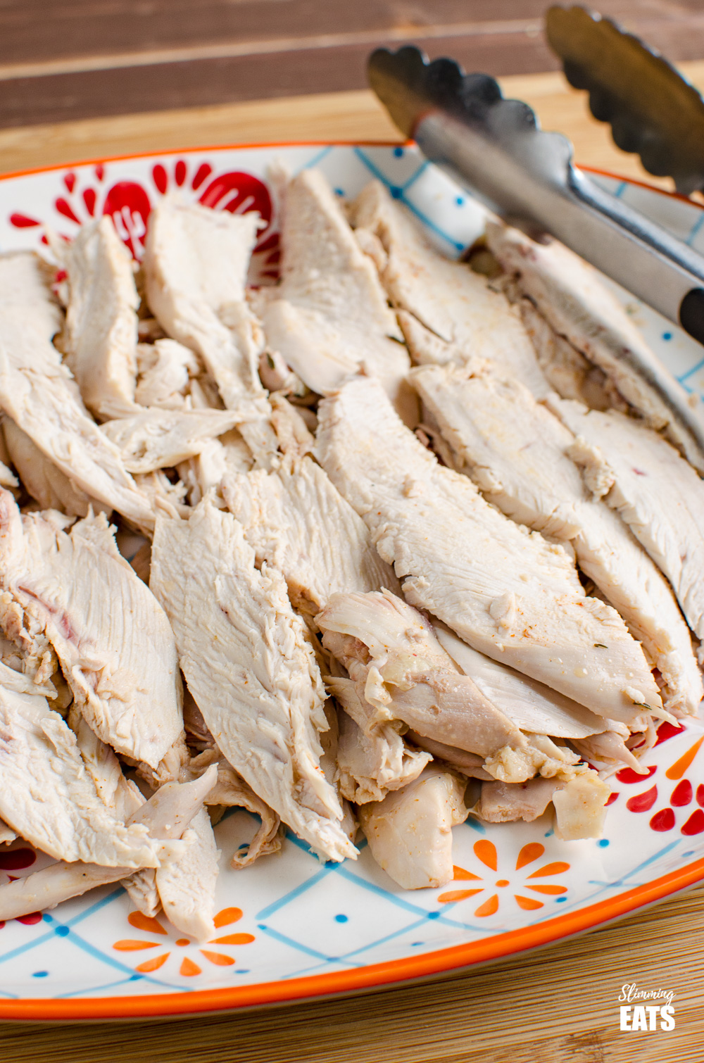shredded sliced instant pot whole cooked chicken on plate with metal tongs