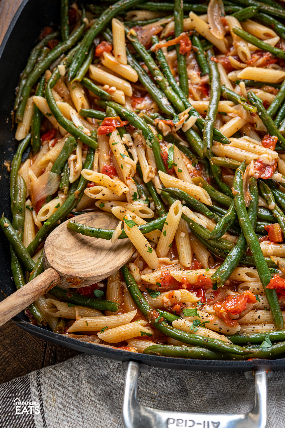 close up of Roasted Green Bean and Tomato Pasta in all clad square skillet with olive wood spoon