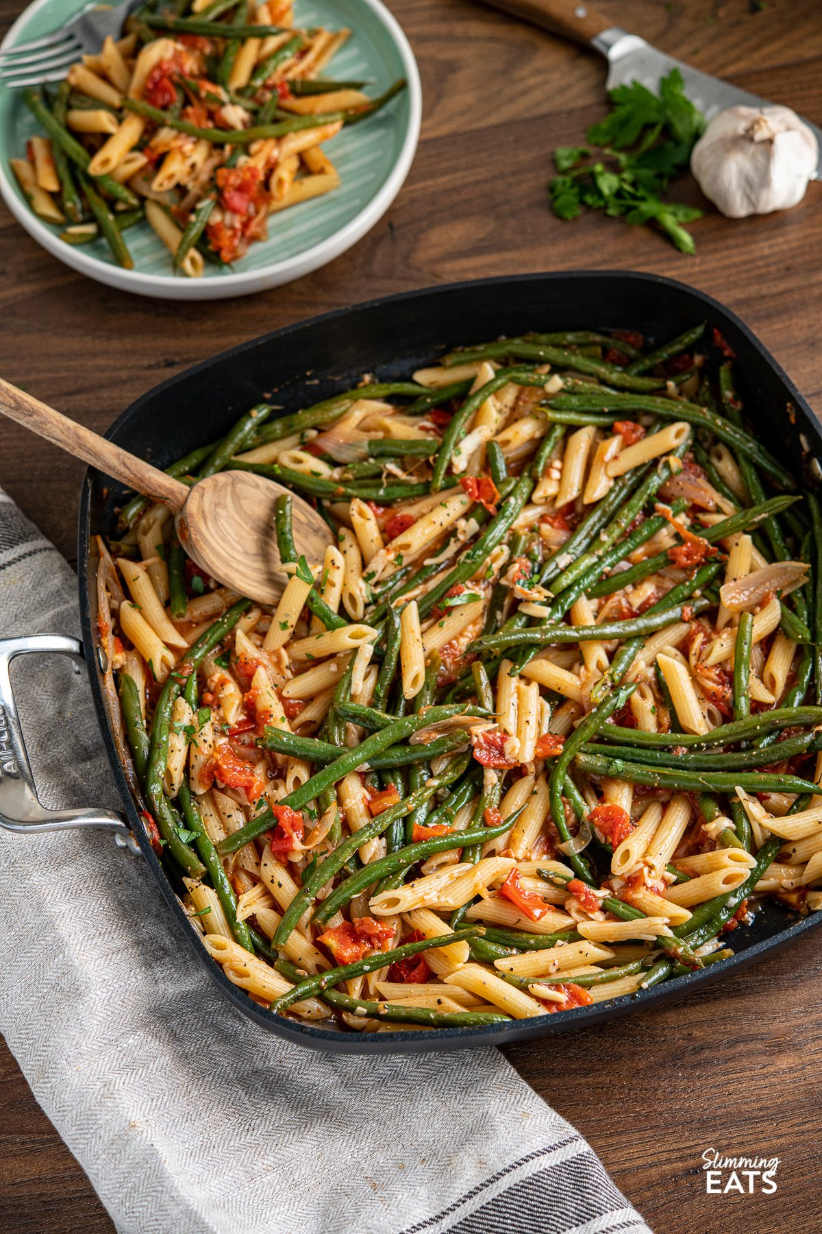 Roasted Green Bean and Tomato Pasta in all clad square skillet with olive wood spoon, fresh garlic and parsley in background as well as plat e with serving of pasta