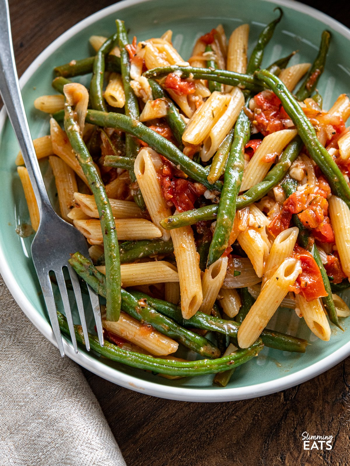 close up of serving of Roasted Green Bean and Tomato Pasta on turquoise plate