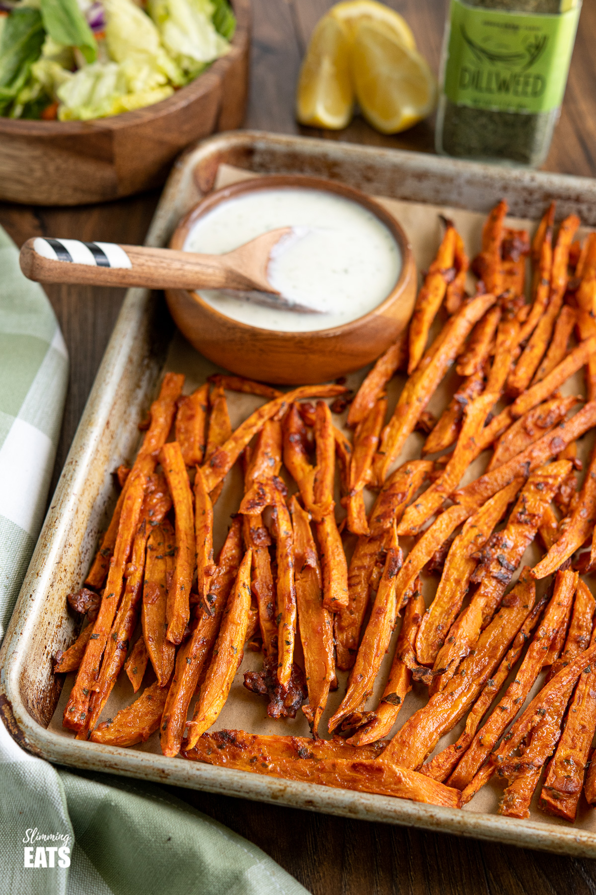 Parmesan Sweet Potato fries on a baking tray lined with parchment paper and with ranch dressing