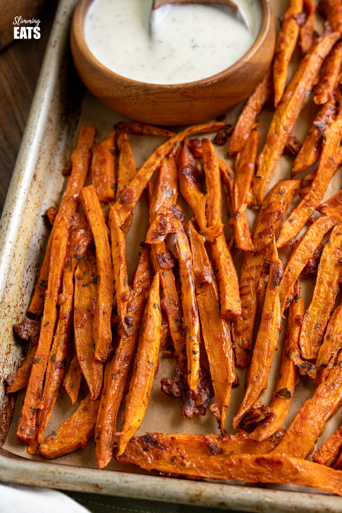 close up of parmesan sweet potato fries on baking tray with wooden bowl of ranch dressing