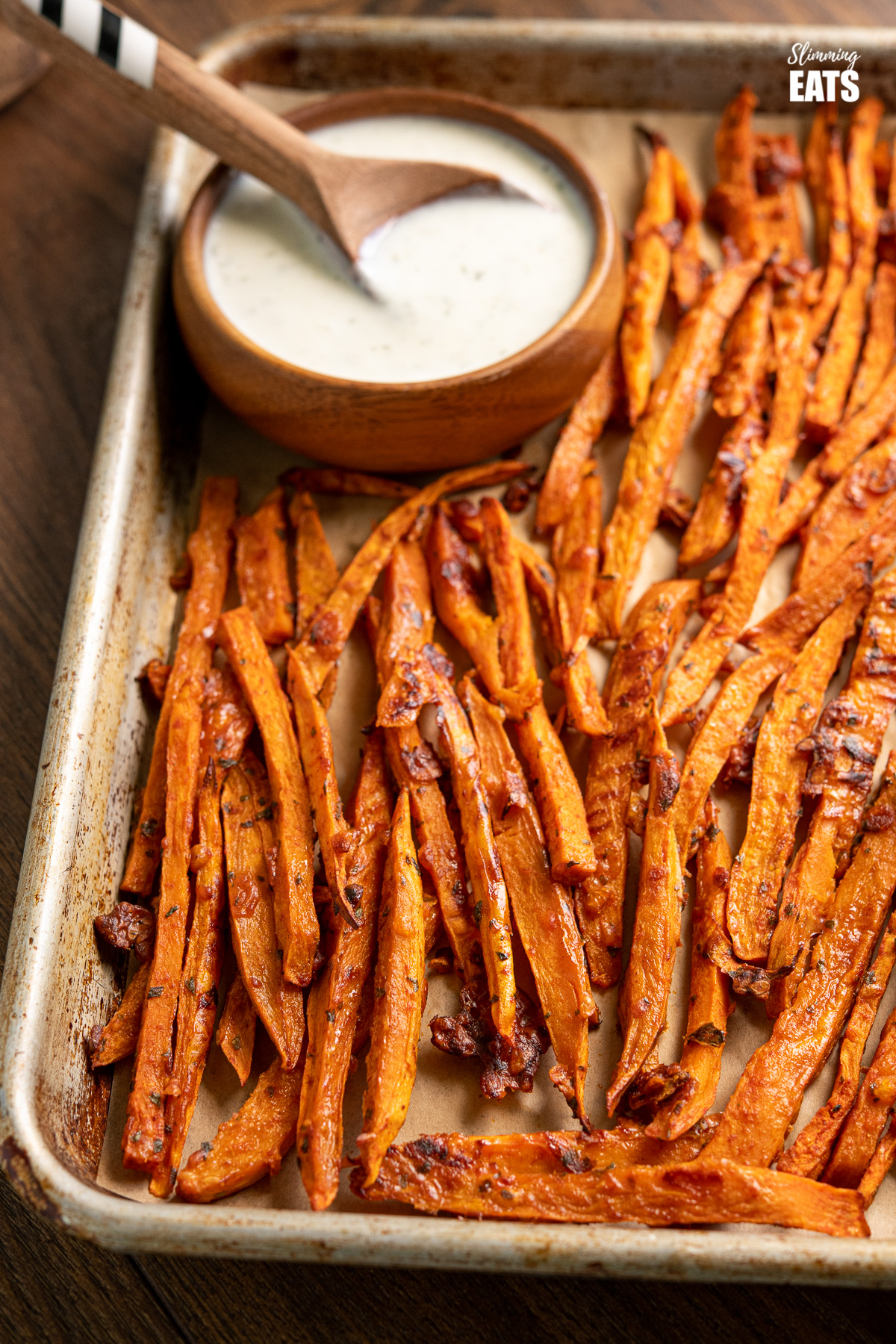 Parmesan Sweet Potato Fries with Ranch Dressing on baking tray with ranch dressing in wooden bowl