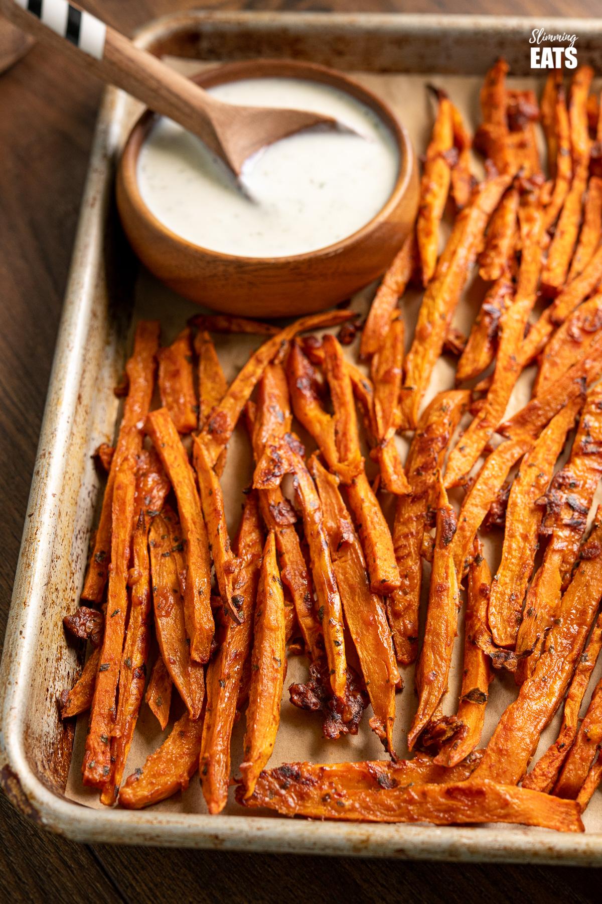 Parmesan Sweet Potato Fries with Ranch Dressing on baking tray with ranch dressing in wooden bowl