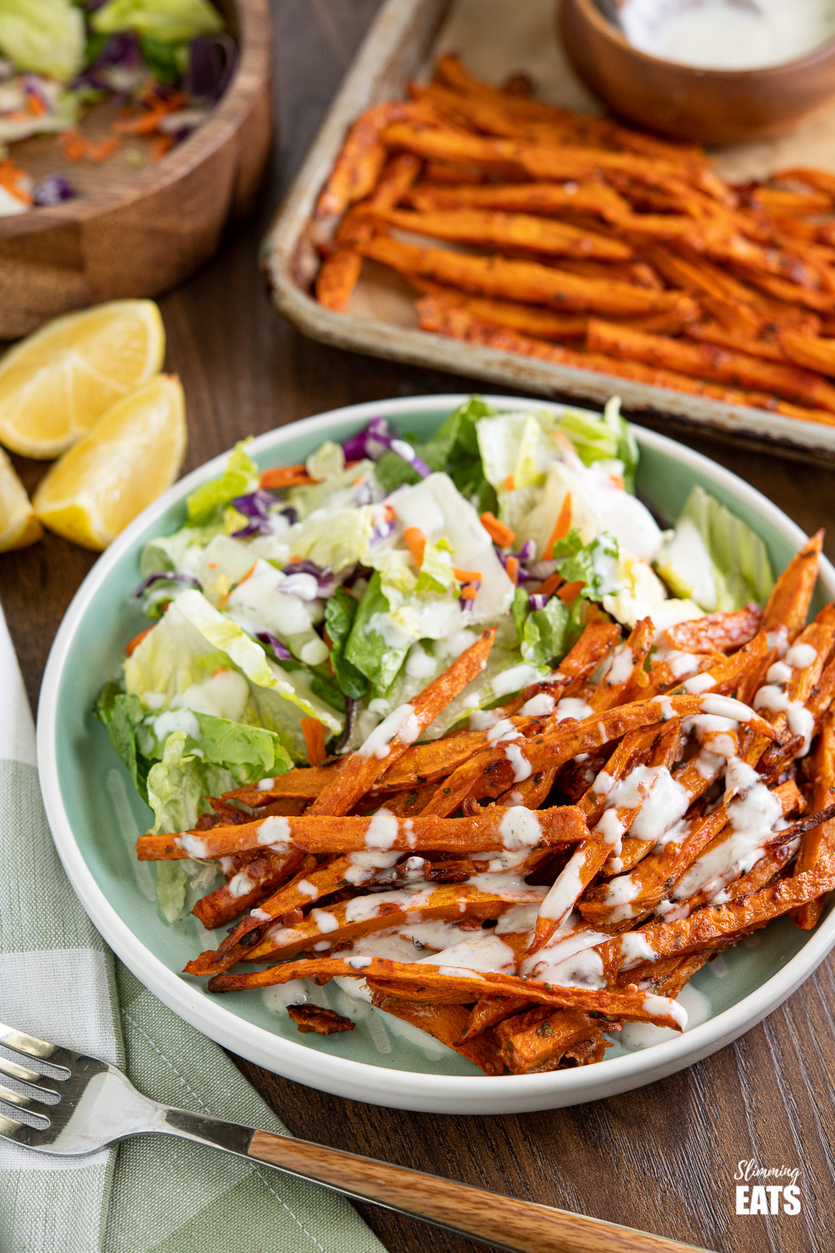 Parmesan Sweet Potato Fries on light teal plate with salad and ranch dressing, lemon slices and tray of sweet potato fries in background