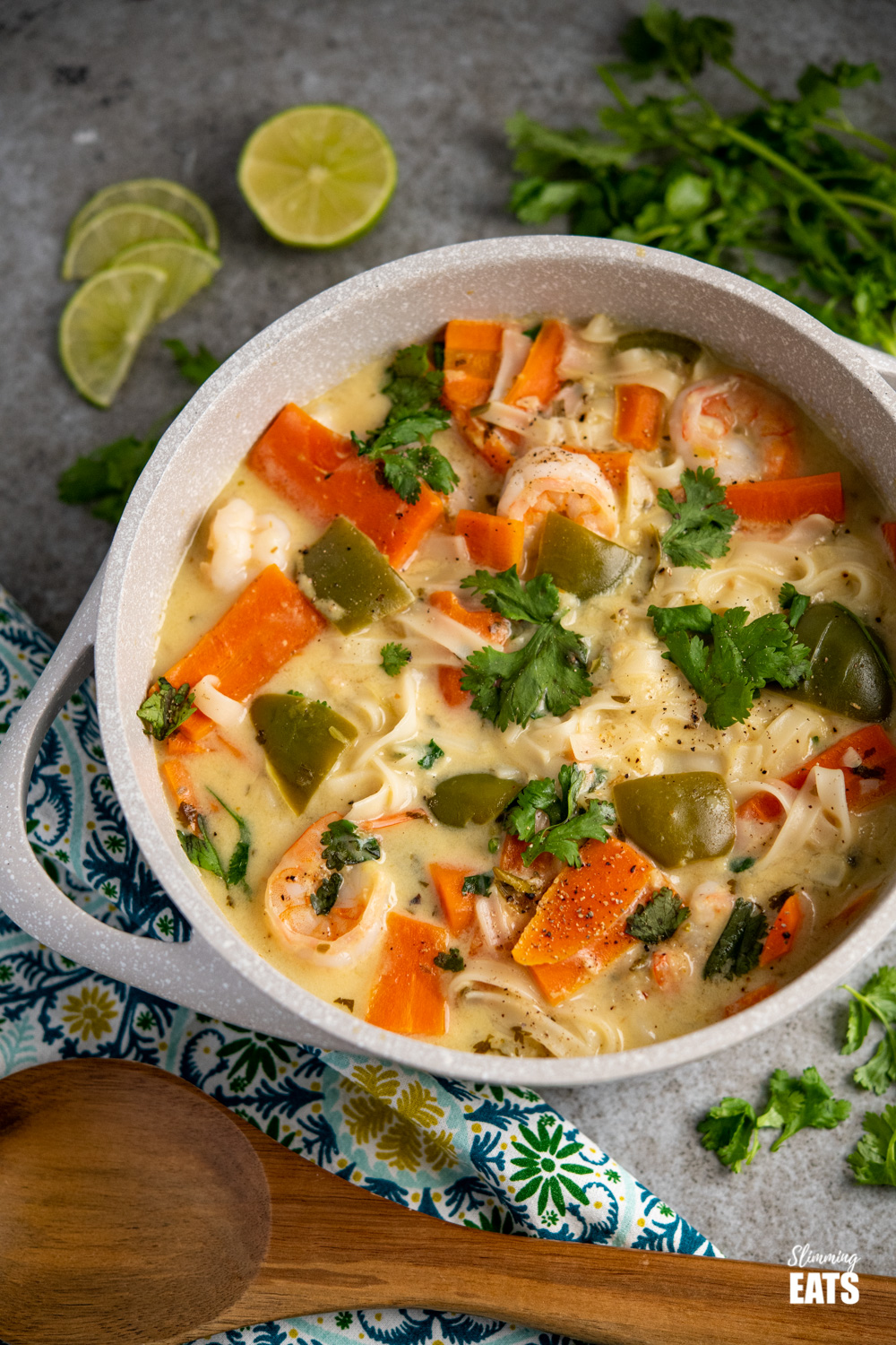 Thai Coconut Shrimp Noodle Soup in grey speckled ceramic pan with scattered lime slices and cilantro