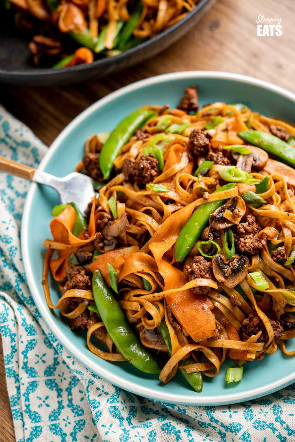hoisin beef noodles on turquoise plate with fork