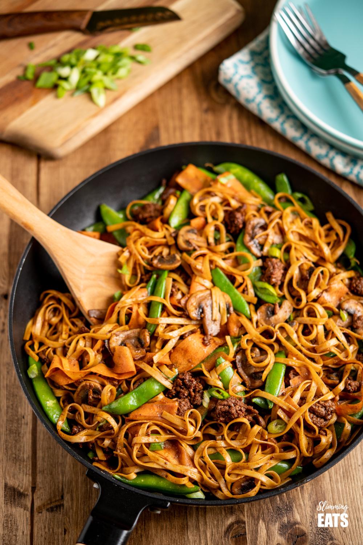 hoisin beef noodles in black frying pan with wooden spoon