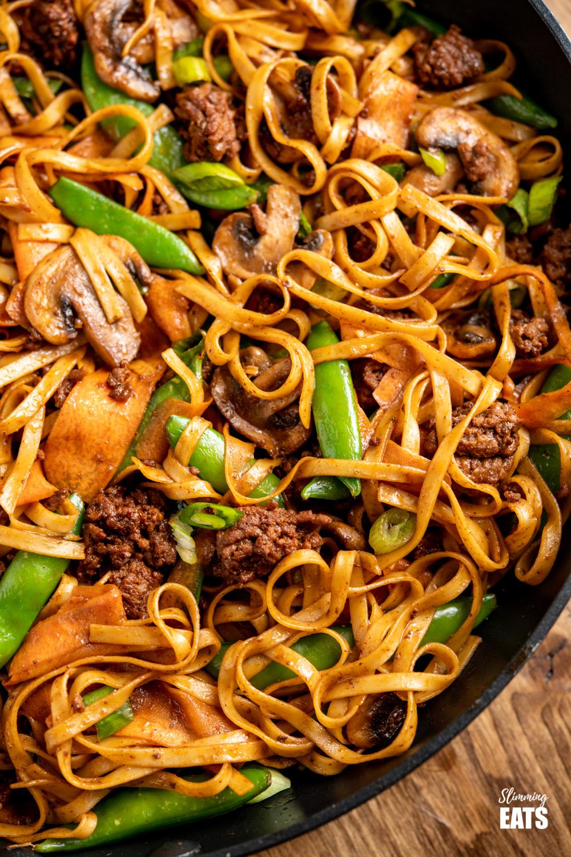 close up of hoisin beef noodles in black frying pan