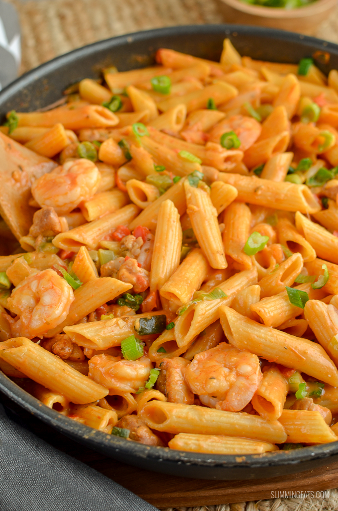 New Orleans Cajun Pasta in frying pan with wooden spoon - shrimp, chicken and pasta visible in pan.