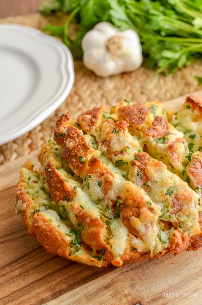 Pull-Apart Cheesy Garlic Oat Bread on wooden board with white plate, garlic and herbs in background