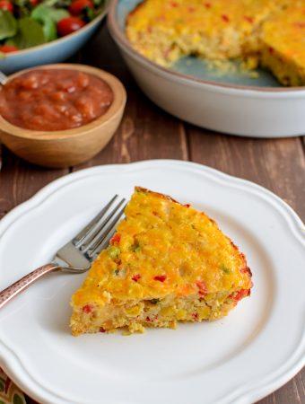 slice of lentil cheddar sweetcorn bake on plate with salad and salsa
