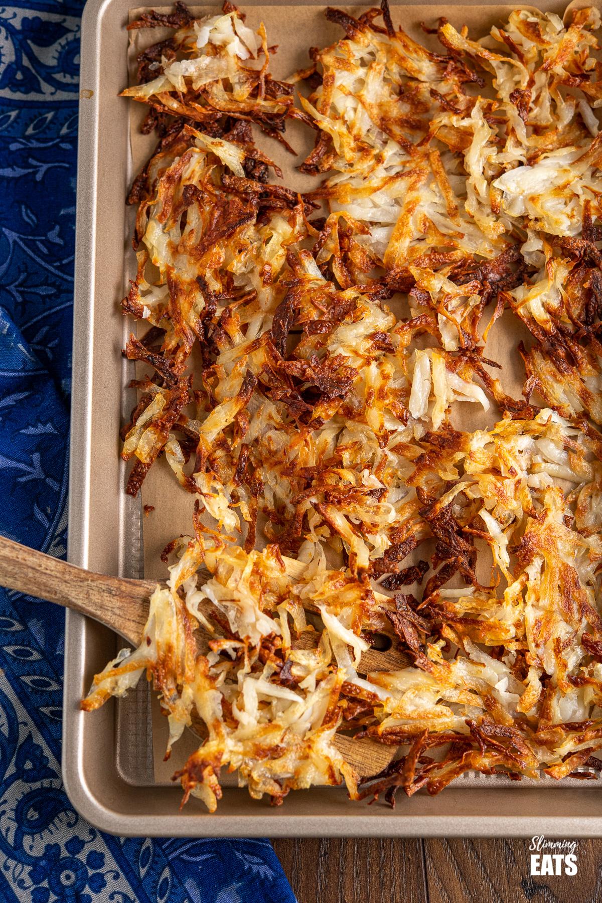 shredded potato hash browns on baking tray