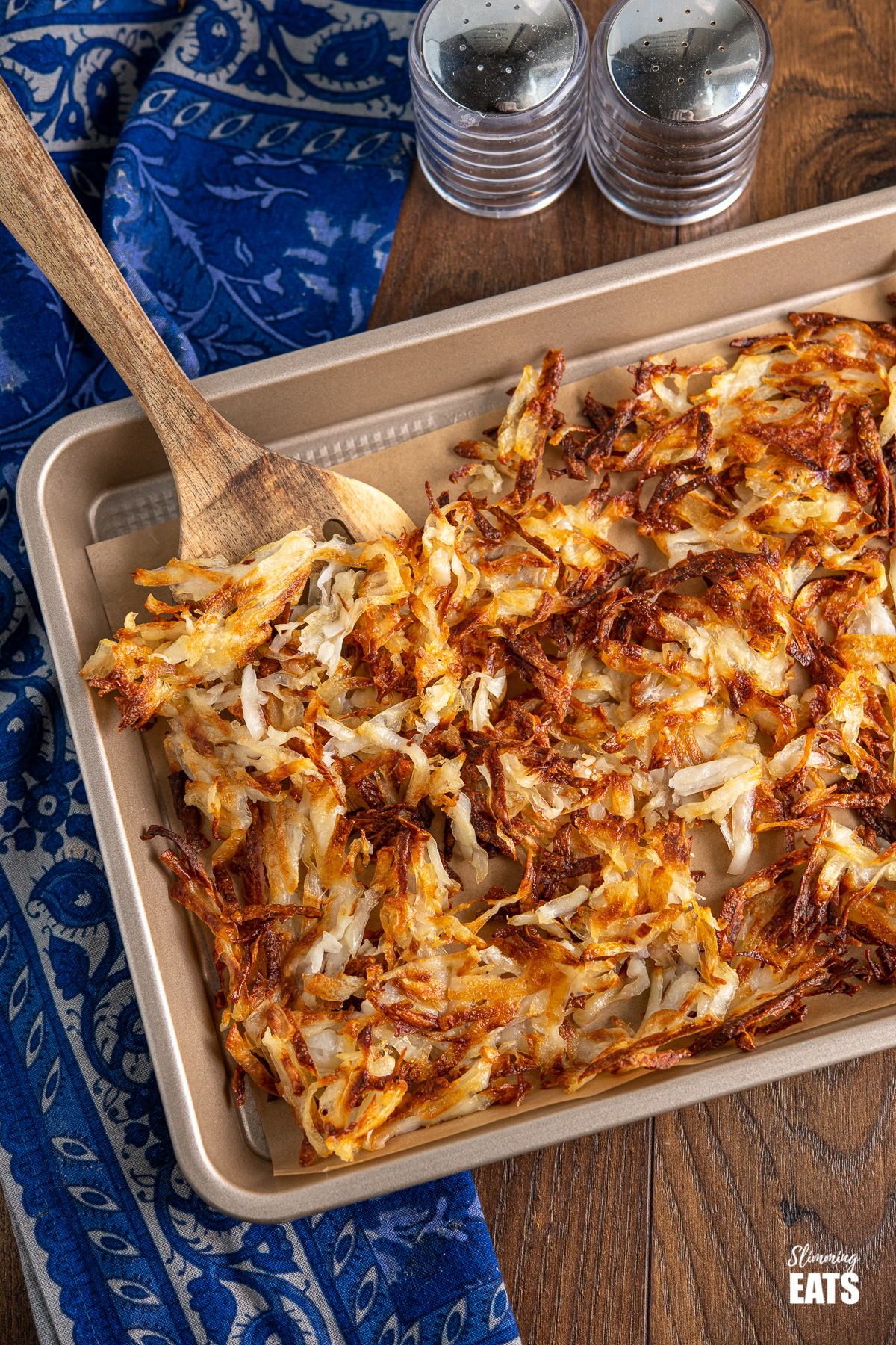 crispy golden sheet pan hash browns on a baking tray with parchment