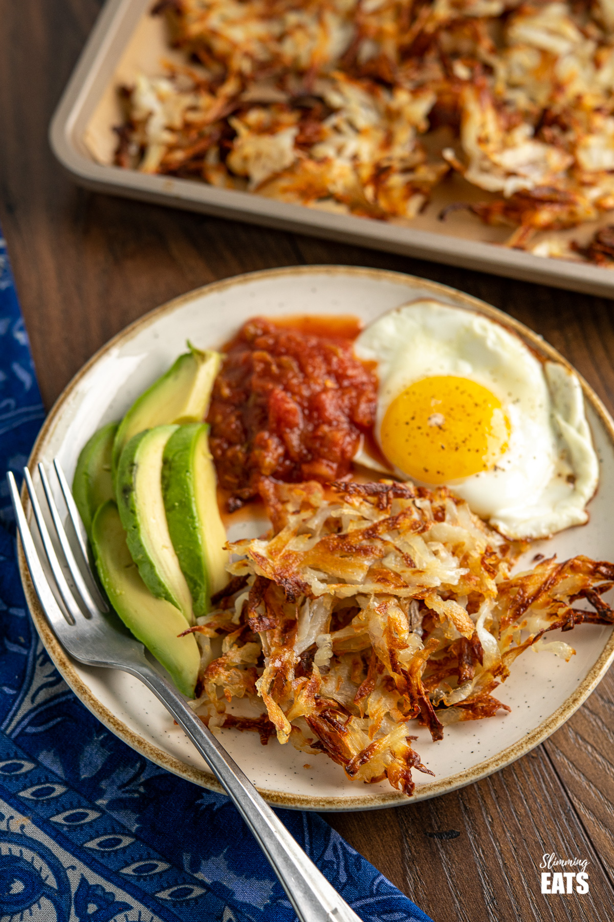 shredded potato hash browns on white plate with egg, salsa and avocado, fork placed to the side and tray of hash browns in the background