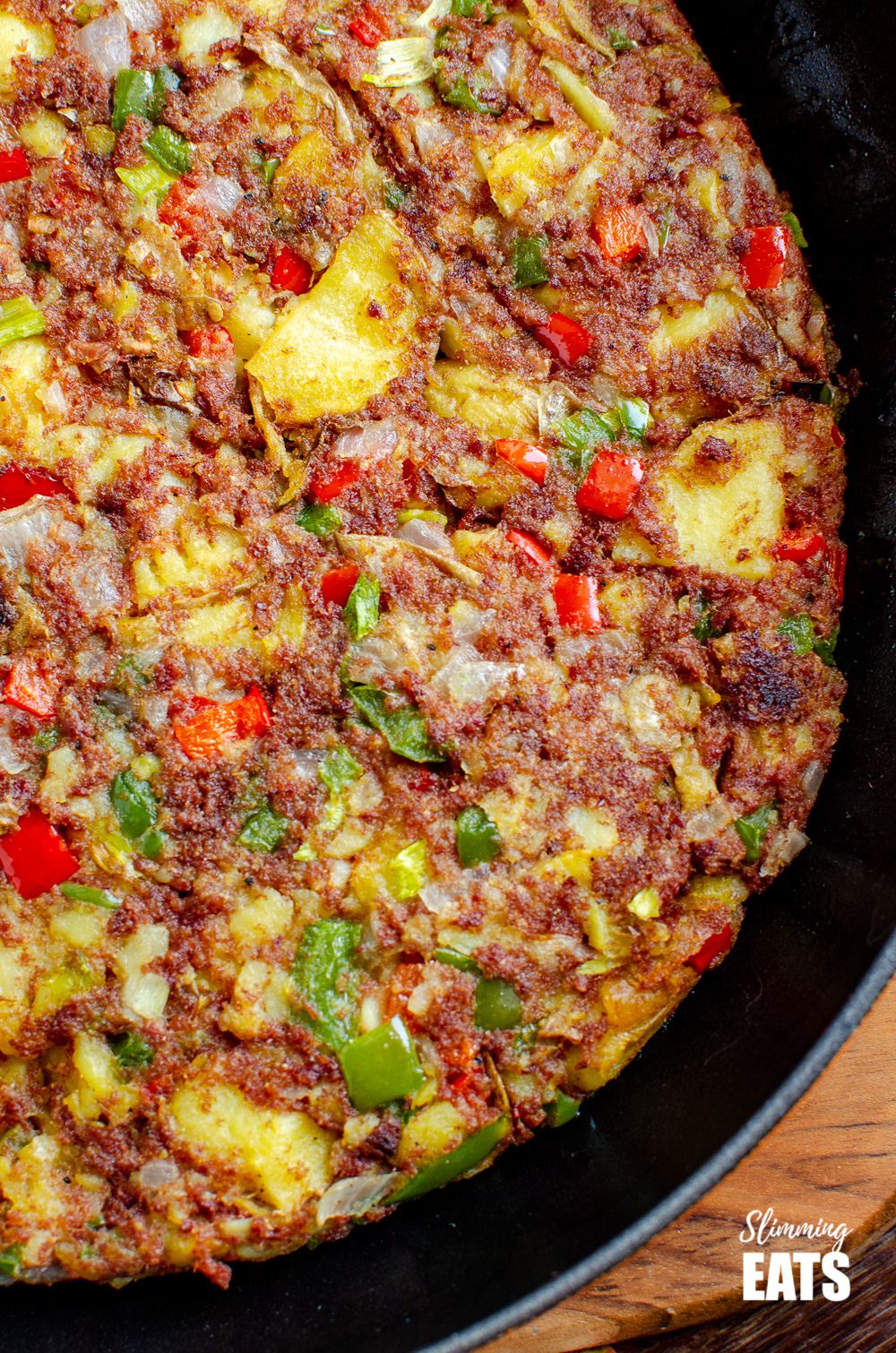 close up corned beef hash in a orange le creuset skillet on wooden board