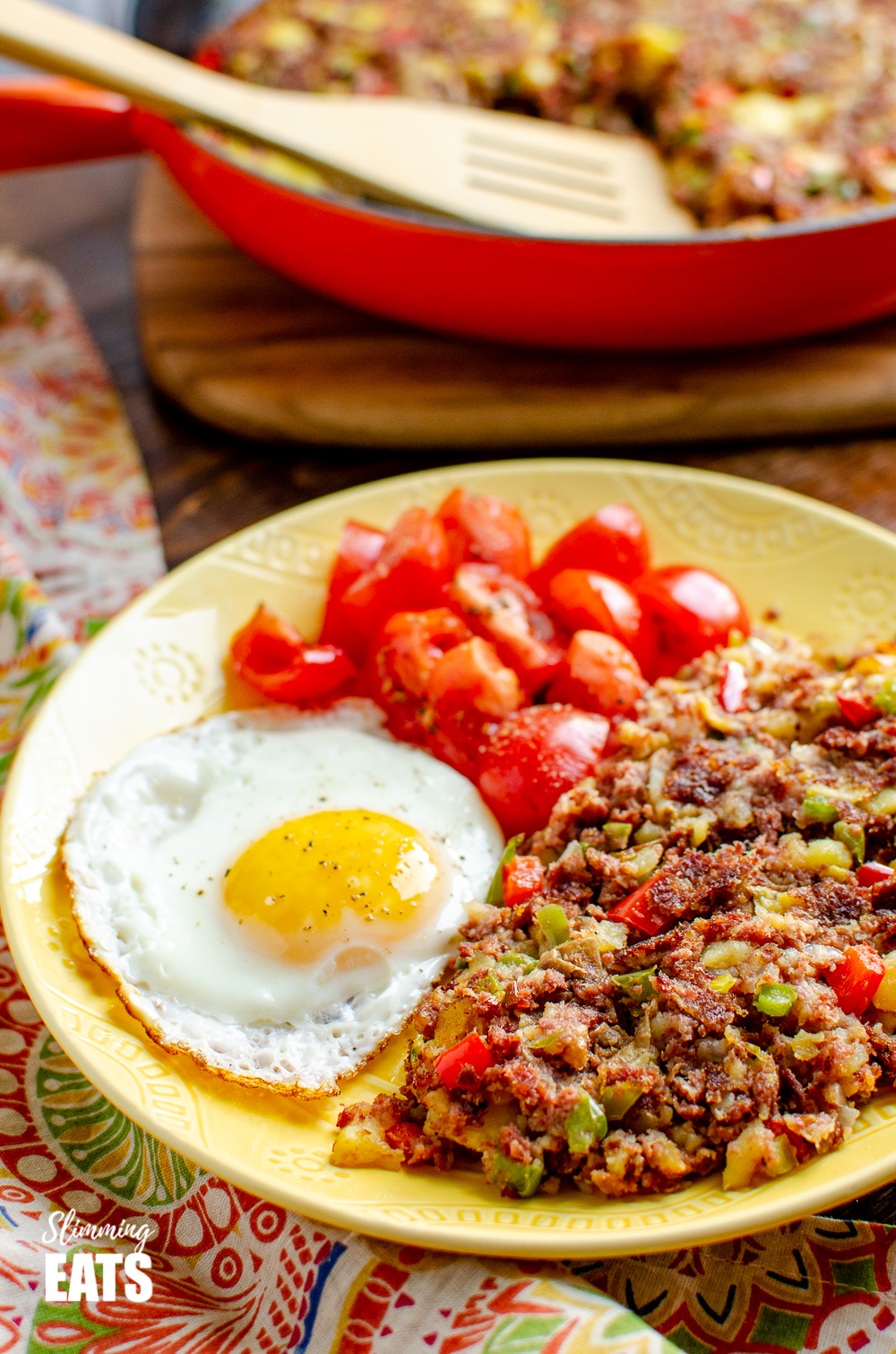 corned beef hash on a yellow plate with fried egg and tomatoes