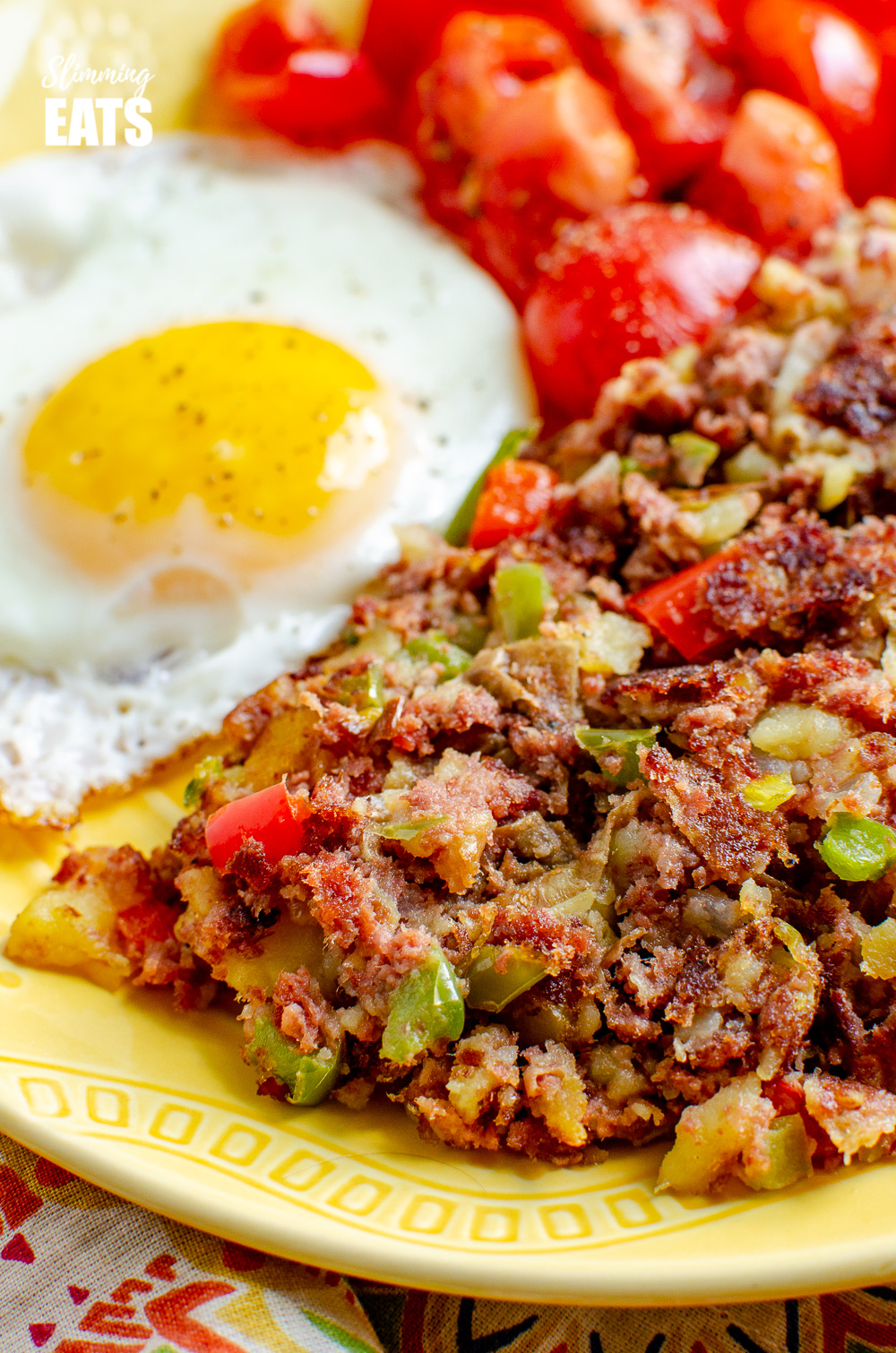 close up of corned beef hash on a yellow plate with fried egg and tomatoes
