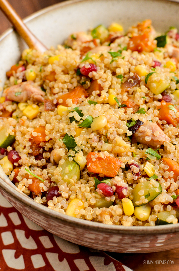 close up of Roasted Butternut Squash Chicken Quinoa Salad in beige bowl with pomegranate and zucchini