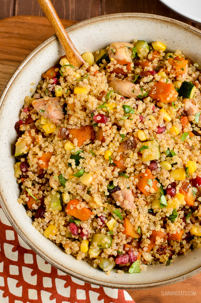 Roasted butternut squash chicken quinoa salad in beige bowl with spoon on a wooden board