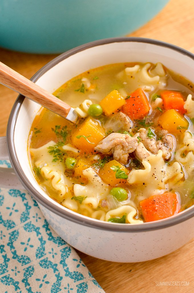 close up of chicken pasta soup in mug with spoon