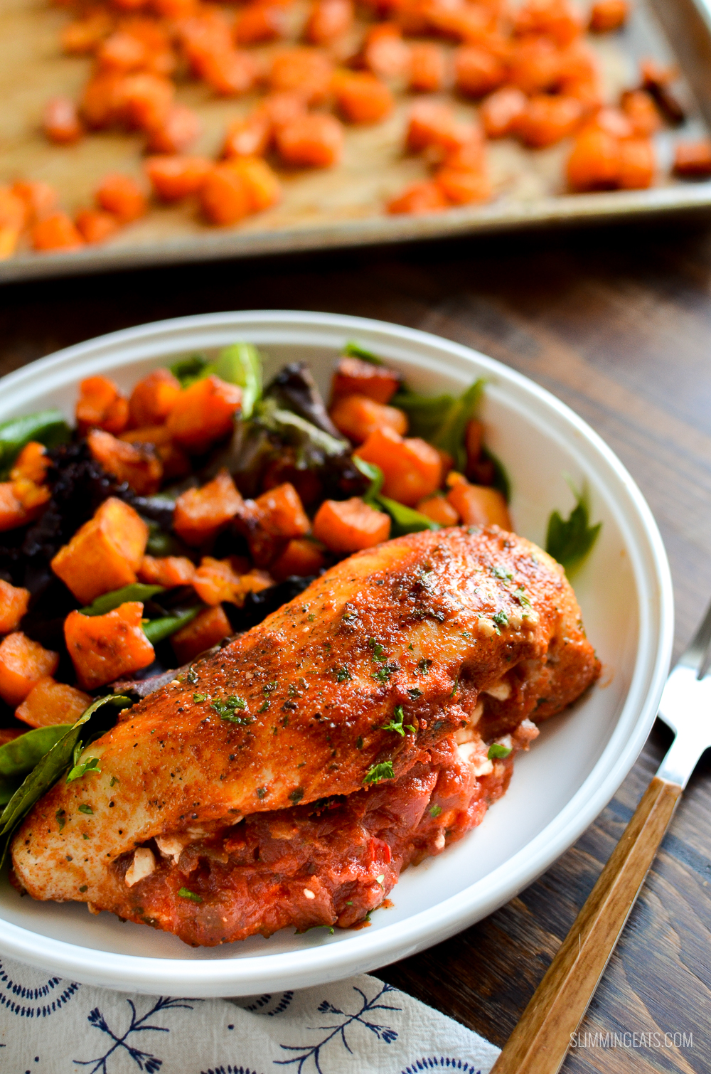 spicy chicken stuffed with feta cheese and salsa on white bowl with baby greens and roasted squash