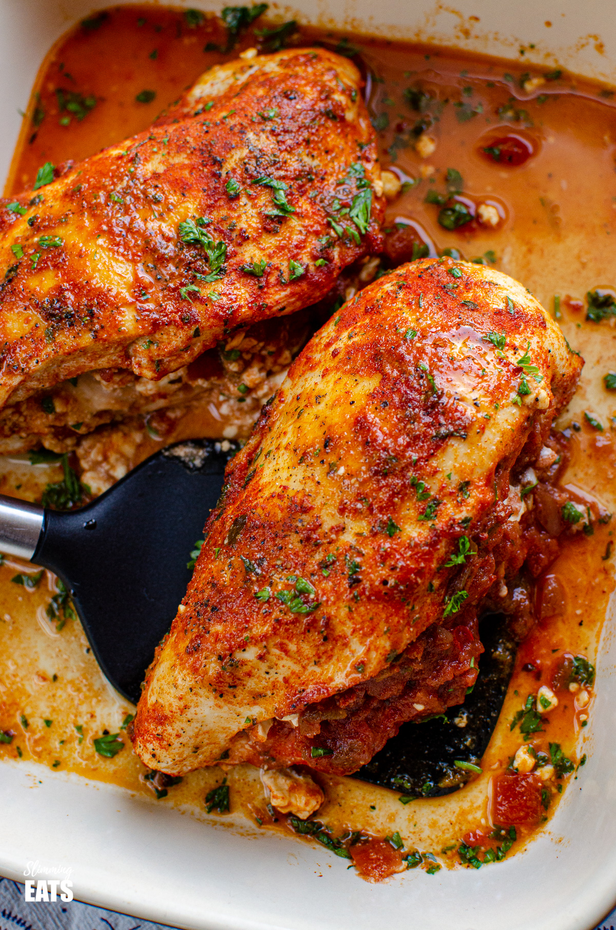 close up of Spicy Chicken Stuffed with Feta Cheese and Salsa in baking dish