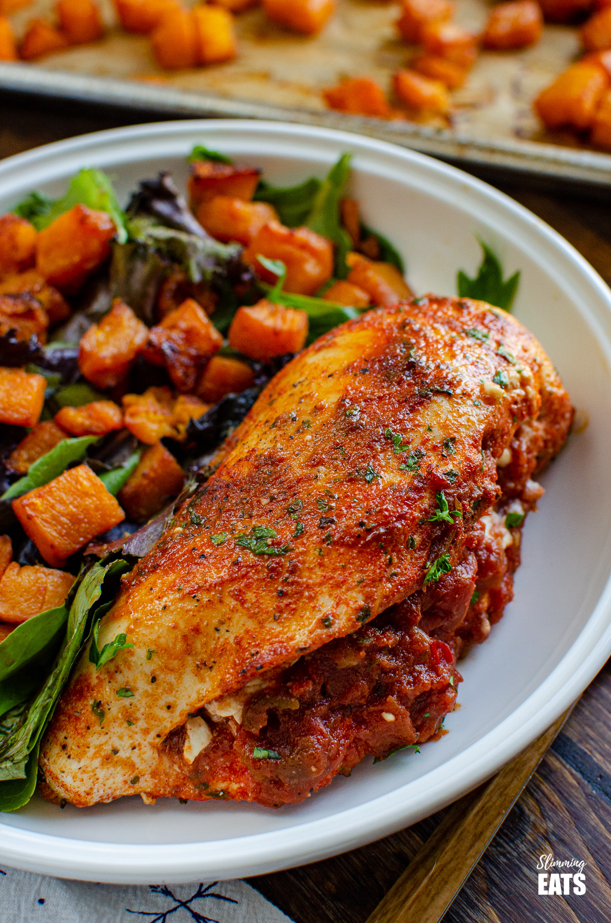 Spicy Chicken Stuffed with Feta Cheese and Salsa in bowl with roasted squash and salad