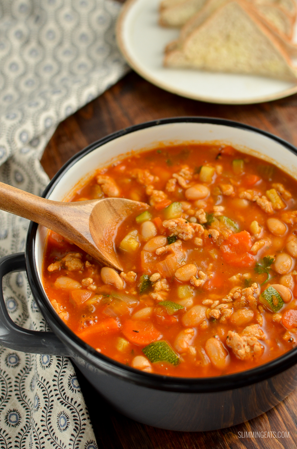grey saucepan of Syn Free ground turkey vegetable bean soup with bread and butter on plate