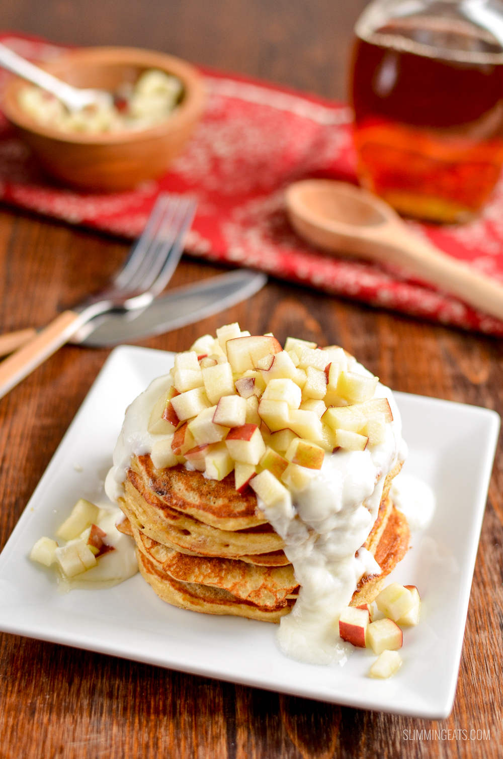 mince pie pancakes stack on white plate topped with apple, yoghurt and maple syrup