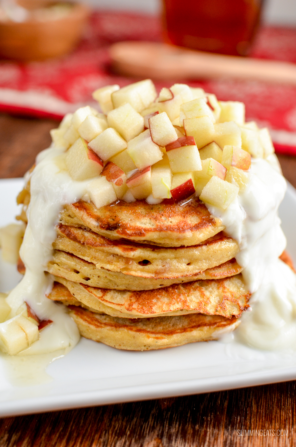 stack of mince pie pancakes on white plate topped with apple, yoghurt and maple syrup