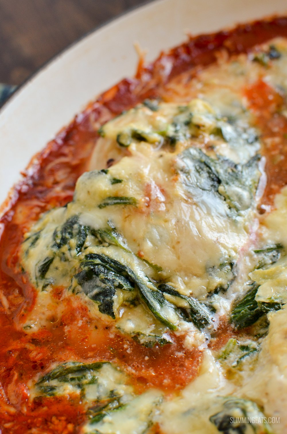 ricotta spinach topped chicken breasts in skillet with tomato sauce
