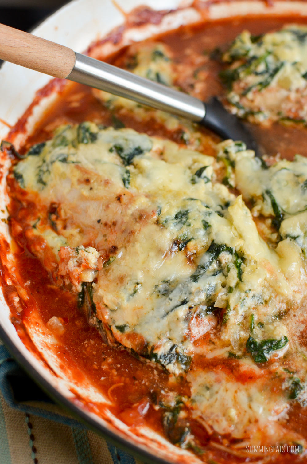 spinach ricotta topped chicken with tomato sauce in skillet with spatula