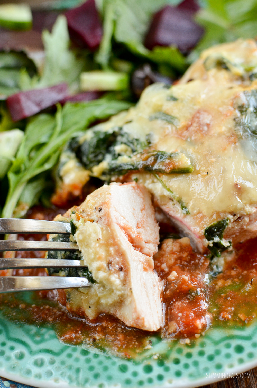 ricotta spinach topped chicken bread sliced into on a fork with tomato sauce