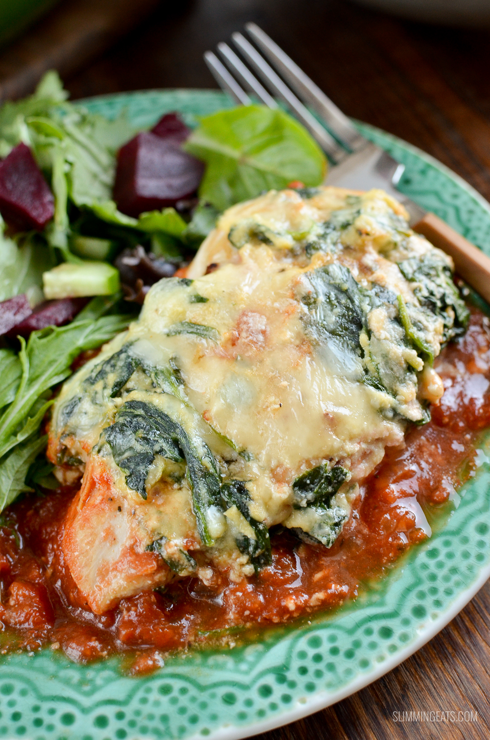 close up of ricotta spinach topped chicken on green plate with salad