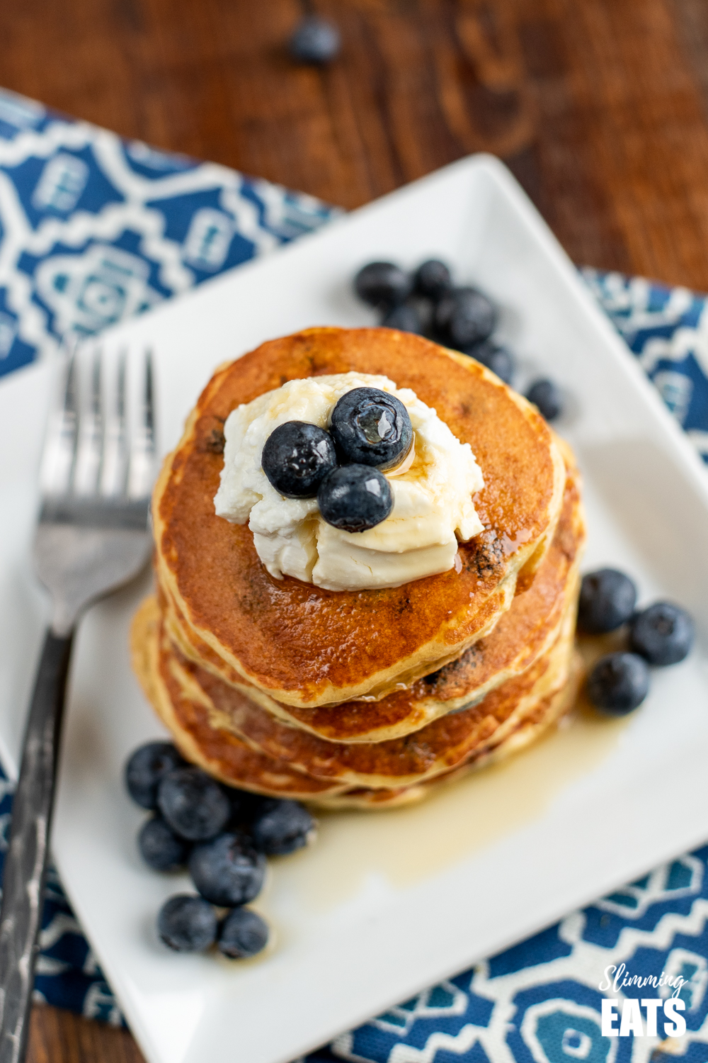 over the top view of lemon blueberry oat pancakes on a white plate with blueberries and quark