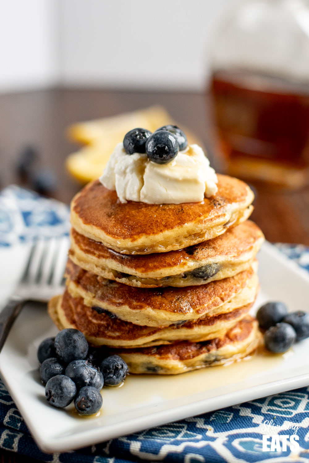 stack of lemon blueberry oat pancakes on a white plate topped with quark, blueberries and maple syrup