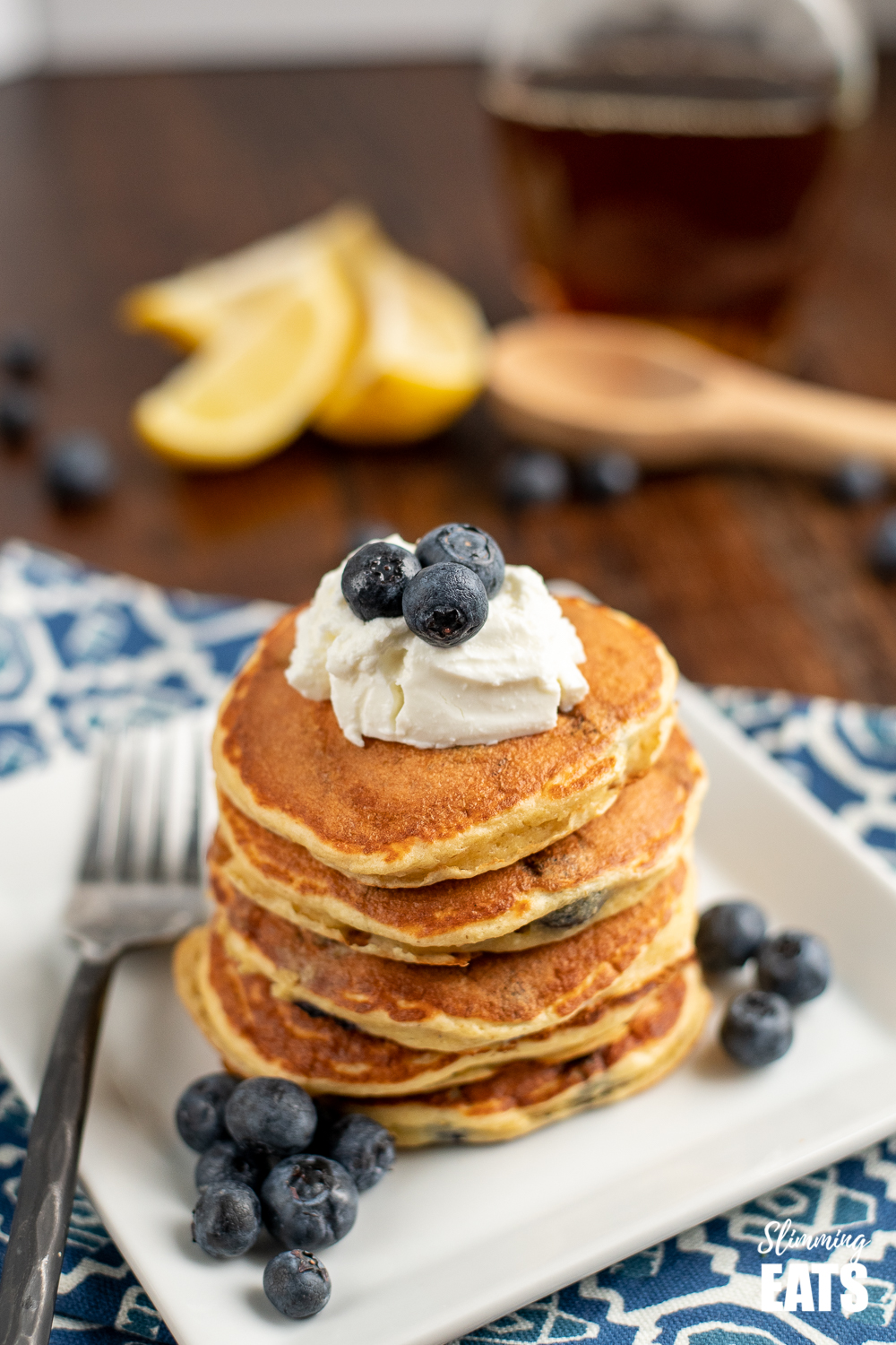 lemon blueberry oat pancakes on a white plate topped with quark and fresh blueberries