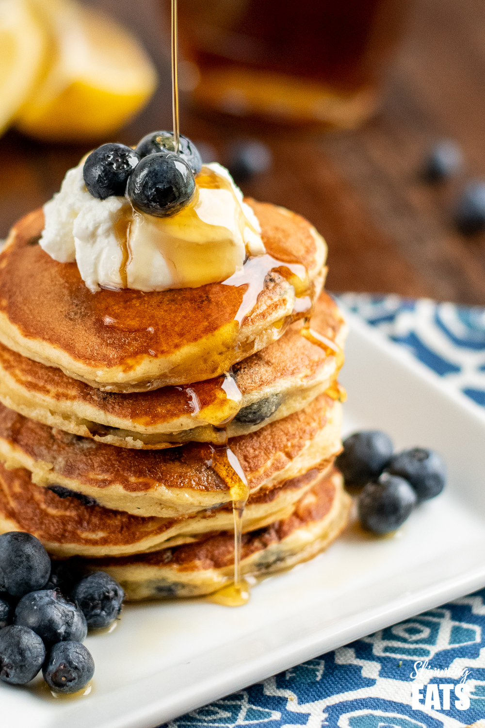close up of maple syrup being drizzled over lemon blueberry oat pancakes on white plate