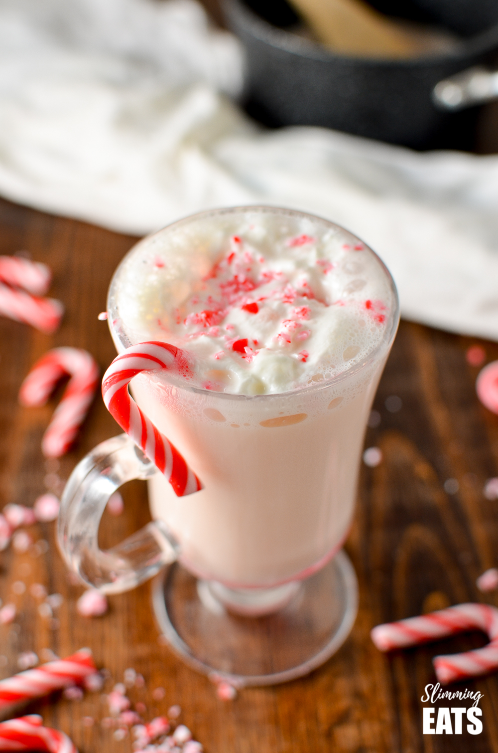 candy cane white hot chocolate in glass mug with candy cane piece on edge of mug