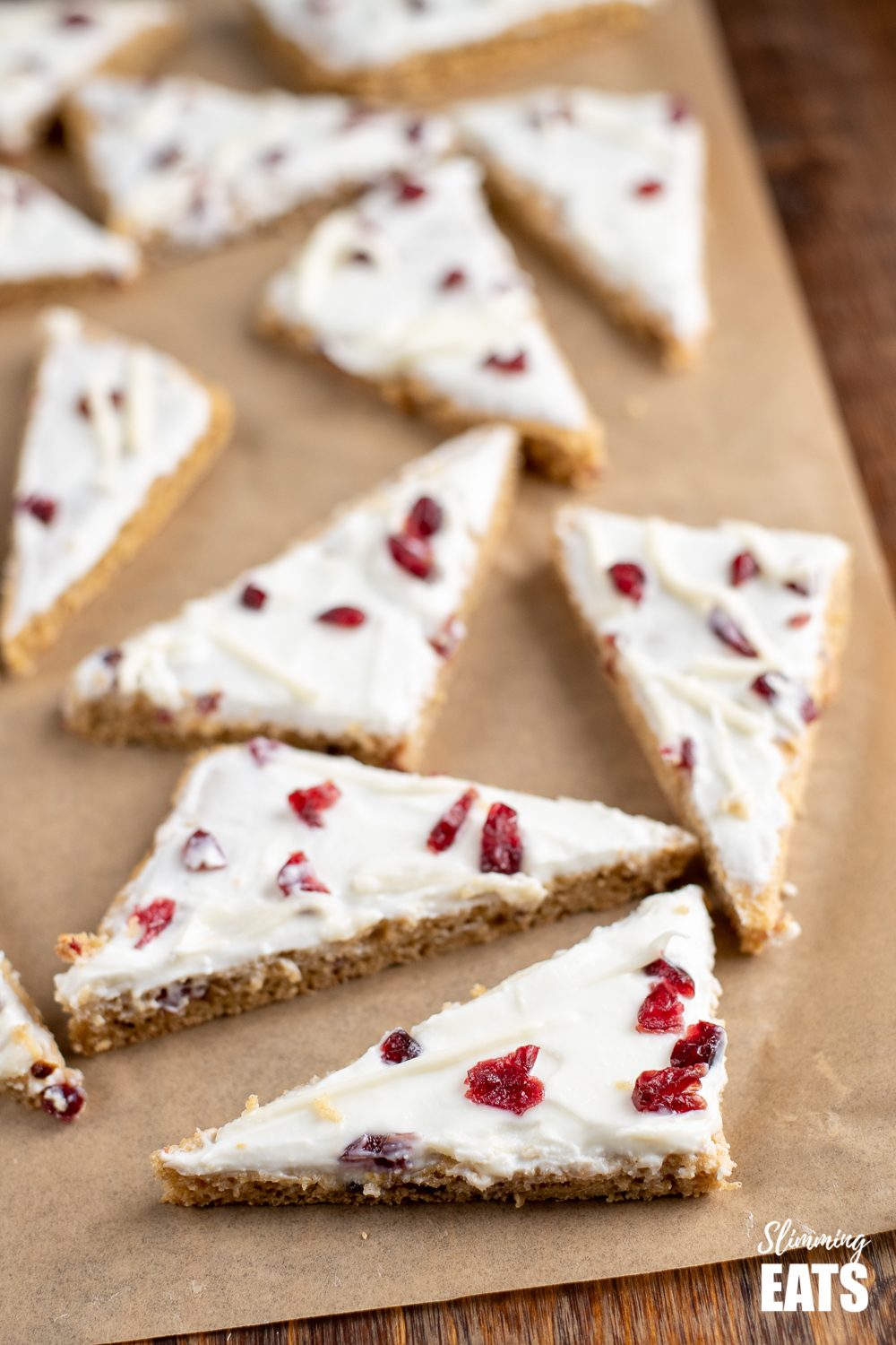 cranberry bliss baked oat bars on parchment paper