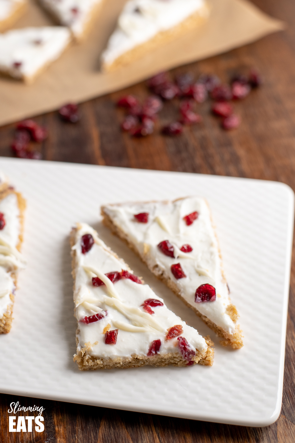 cranberry bliss baked oat bars on a white plate with scattered cranberries