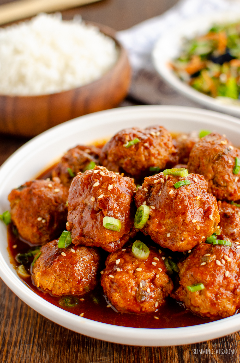 Firecracker Chicken Meatballs in white bowl sprinkled with spring onion and sesame seeds
