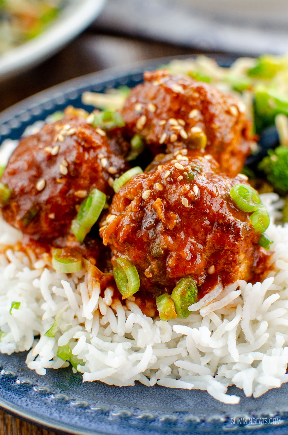 close up of firecracker chicken meatballs on blue plate with rice and stir fried vegetables