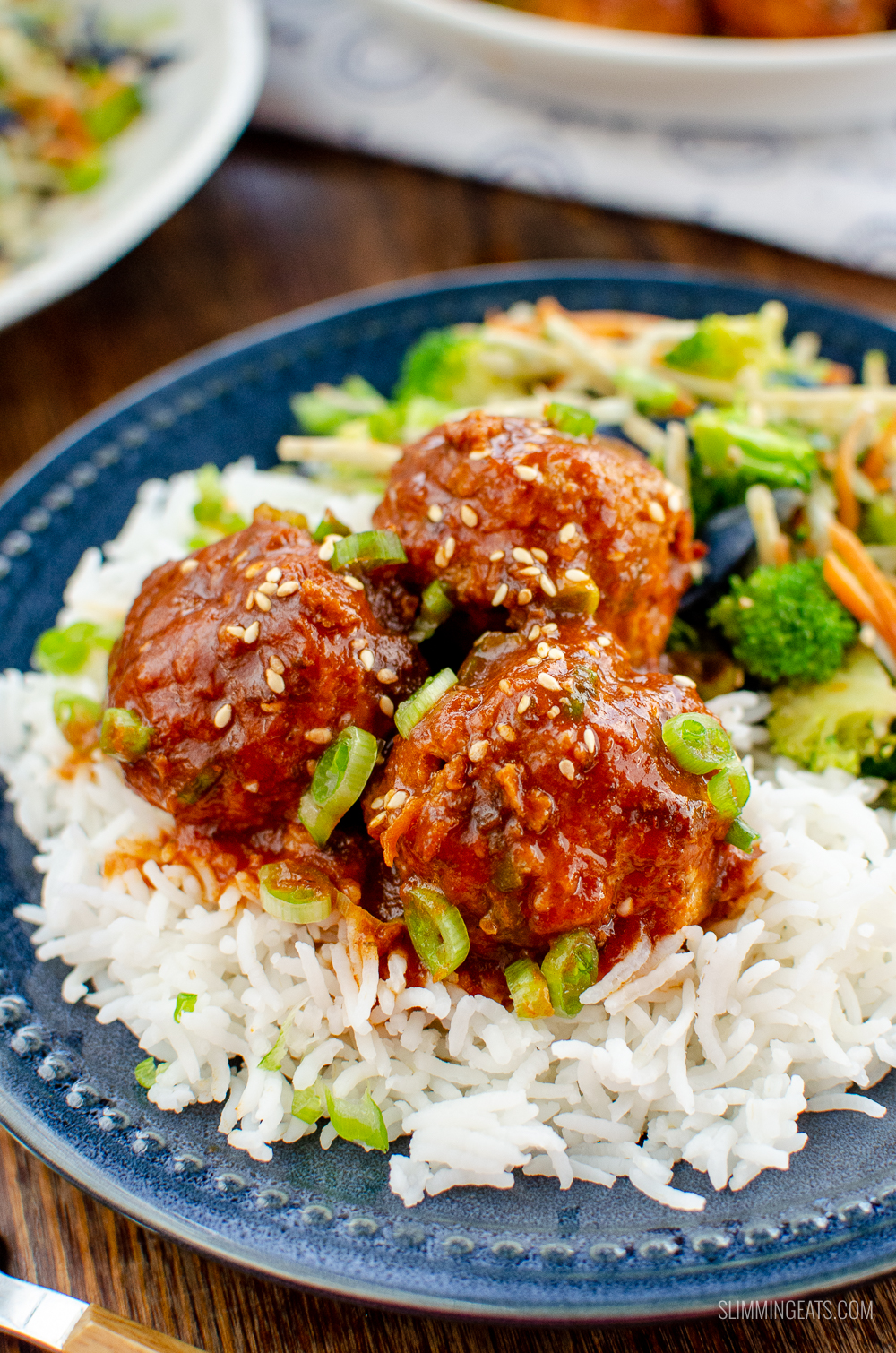 firecracker chicken meatballs on blue plate with rice and vegetables
